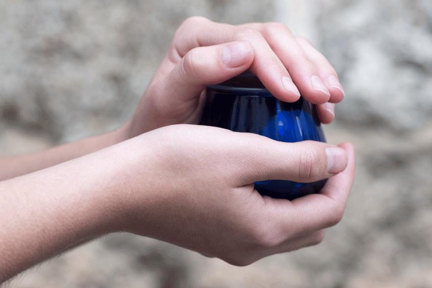 Copa de cata de aceite de oliva calentándose con las manos